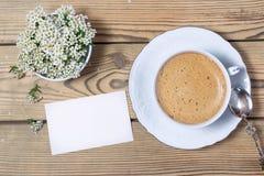 Weinlesetasse kaffee, -anmerkung und -blumen auf Holztisch Lizenzfreies Stockbild