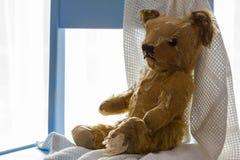 Weinleseteddybär, der auf blauem Kindertagesstättenstuhl sitzt stockbild