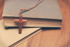Weinleseton der hölzernen christlichen Kreuzkette auf heiliger Bibel Stockbild