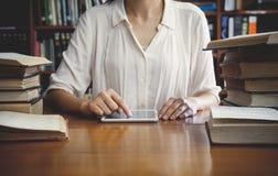 Weinleseton der jungen Studentin mit Tablette im Buchladen Stockbild