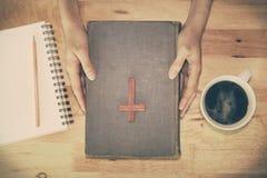 Weinleseton des hölzernen christlichen Kreuzes auf der Bibel Stockbild