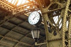Weinleseuhr und -laterne auf Bahnhof mit Gebäudedach stockfotografie