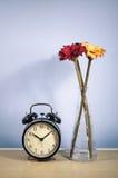 Weinleseuhr- und -Vasenblumen Lizenzfreie Stockfotos