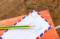 Weinleseumschlag, -bleistifte, -notizbuch und -gläser auf einem Holzfußboden Stockfoto