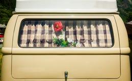 Weinlesevorhang auf dem Fenster eines alten Packwagens mit Blume Stockfoto