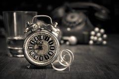 Weinlesewecker, der fünf zum Mitternacht und zu einem alten Telefon zeigt H Stockfotografie