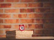 Weinlesewecker und alte Bücher auf Holztisch Lizenzfreie Stockfotos