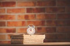 Weinlesewecker und alte Bücher auf Holztisch Lizenzfreies Stockfoto