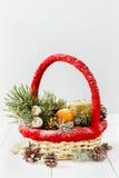 Weinleseweihnachten oder Weihnachtszusammensetzung Korb mit Tangerinen, Kiefernkegel, goldenen Bällen, Tannenzweigen und Kerze Stockfotos