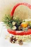 Weinleseweihnachten oder Weihnachtszusammensetzung Korb mit Tangerinen, Kiefernkegel, goldenen Bällen, Tannenzweigen und Kerze Stockfotografie