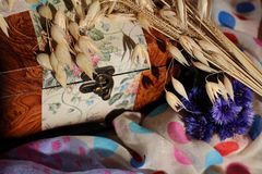 Weinleseweinlesekasten auf mehrfarbigen Geweben mit Blumen stockfotos