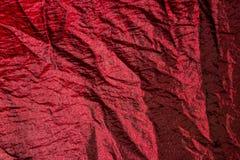 Weinrot zerknitterte Gewebe auf einem Bett mit Schatten Stockbild