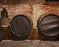 Weintonnefässer und -flasche gestapelt im alten Keller Lizenzfreie Stockbilder