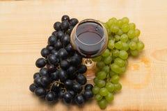 Weintrauben und ein Glas Wein auf einem hölzernen Hintergrund stockfotos