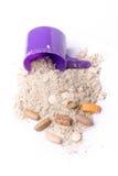 Weiproteïnepoeder in lepel met vitaminen en Stock Afbeeldingen