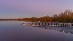 Weir της λίμνης κατά τη διάρκεια του ηλιοβασιλέματος στοκ εικόνες