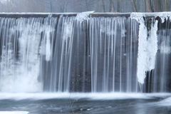 Weir with ice. Water falling down from the weir with some icicles in winter Stock Photos
