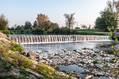 Weir on Olse river in Karvina. With trees and clear sky Royalty Free Stock Image