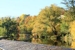 Weir of river Malse. Weir on river Malse with stones and colorful autumn trees in Rimov, Czech Republic Stock Image