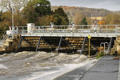 Weir and sluice gate on the River Thames. Swollen river Thames passing through a Weir and sluice Royalty Free Stock Images
