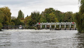Weir and sluice gate on a swollen River Thames Royalty Free Stock Images