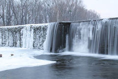 Weir in winter. Water falling down from the weir with some icicles in winter Royalty Free Stock Photos