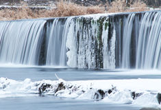 Weir in winter. Water falling down from the weir with some icicles in winter Royalty Free Stock Photography