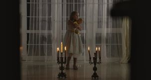 Weird Caucasian girl standing in candlelight with doll. Frightening child looking around. Scare, fear, strangeness.