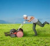Weird gardener.bis. Running senior mowing a green field Royalty Free Stock Photo