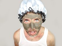 Weird looking man with shower cap and cream on his face horrified seeing himself ugly on bathroom mirror applying facial mask male. Lifestyle funny portrait of Stock Images