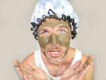 Weird looking man with shower cap and cream on his face horrified seeing himself ugly on bathroom mirror applying facial mask male. Lifestyle funny portrait of Royalty Free Stock Image