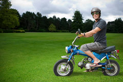 Weird motorcyclist. Strange biker sitting on a blue moped in countryside Stock Photography