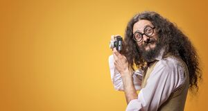 Free Weird Nerd Taking A Photo With A Tiny Camera Royalty Free Stock Image - 179123036