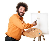 Weird painter starting to paint. Guy in a bright, orange shirt, ready to paint, with a weird smile on his face Stock Photo
