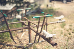 Weird Playground Equipment Art. Old art playground equipment with bicycle seats in scrap art yard. Rusted and seats four. Green handlebars Royalty Free Stock Photography