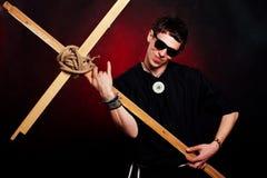 Rocker priest. Weird rocker priest, holding cross like a guitar Royalty Free Stock Photo