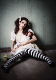 Weird sad young girl with dolls sitting in dirty room Stock Photography