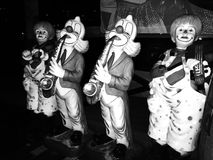 Weird scary clowns in the darkness. Row of weird scary clowns playing instruments Royalty Free Stock Images