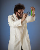 Weird scientist styudying green liquid Stock Images