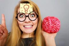 Weird woman holding brain having idea Stock Photo
