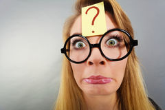 Weirdo nerd woman having question mark on forehead Royalty Free Stock Image