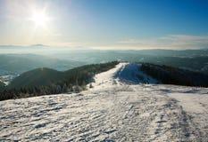 Weise an der Spitze des schneebedeckten Gebirgsrückens auf Sonnenschein und blauem Himmel Lizenzfreie Stockfotografie