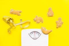 Weisen für verlieren Gewicht sport Plätzchen in Form von Yoga asans nahe stufen ein und misstband auf hellem gelbem Hintergrund stockfoto