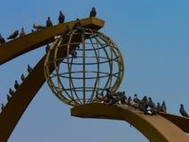 Weite Ansicht von den Tauben, die auf einer Stella in Form eines Balls gegen einen blauen Himmel sitzen lizenzfreie stockfotos