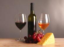 Weiter entwickeltes Stillleben des Weins, des Käses und der Trauben auf Abtropfbrett auf Holztisch Lizenzfreie Stockfotos