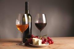 Weiter entwickeltes Stillleben des Weins, des Käses und der Trauben auf Abtropfbrett auf Holztisch Stockfotografie