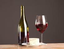 Weiter entwickeltes Stillleben des Weins, des Käses und der Trauben auf Abtropfbrett auf Holztisch Lizenzfreie Stockbilder