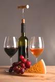 Weiter entwickeltes Stillleben des Weins, des Käses und der Trauben auf Abtropfbrett auf Holztisch Stockbild