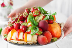 Weiter put plate with fresh fruit mix on table Royalty Free Stock Image