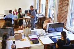 Weitwinkelansicht des beschäftigten Konstruktionsbüros mit Arbeitskräften an den Schreibtischen Lizenzfreies Stockbild